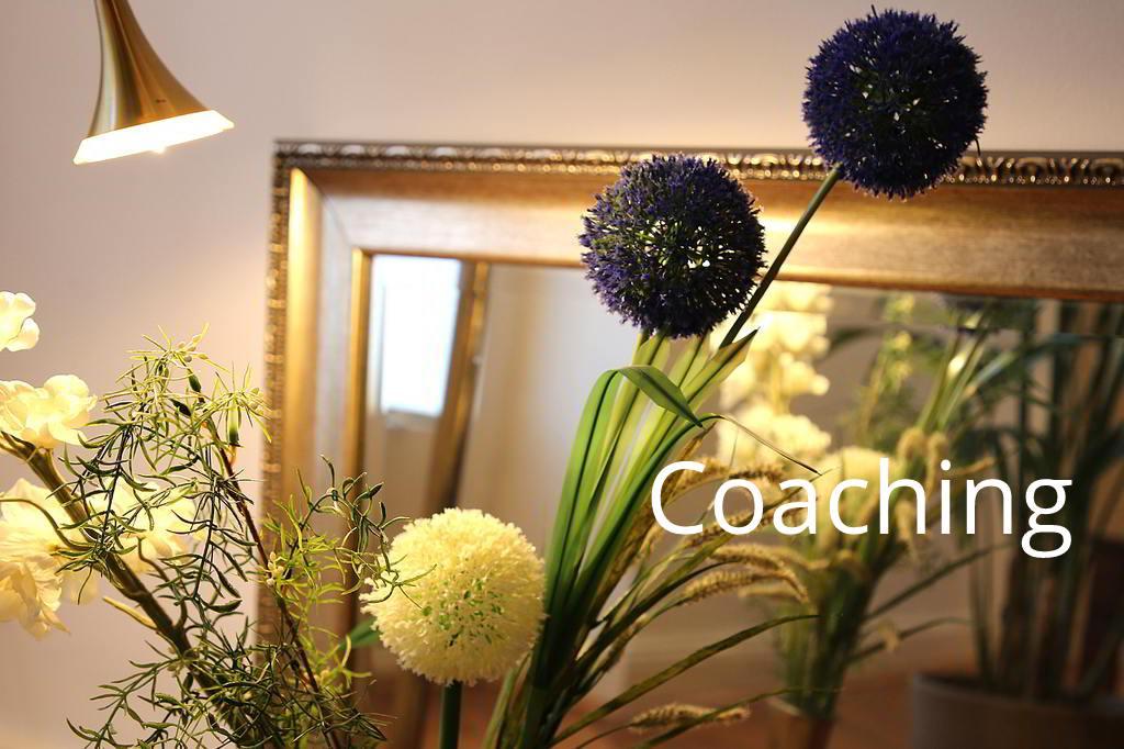 Blumen mit kugeligen Blütenköpfen spiegeln sich in einem Spiegel mit Goldrahmen.