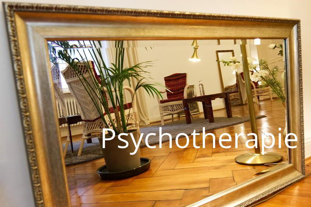 In einem Spiegel mit Goldrahmen sind die Stühle der Praxis Prof. Dr. Anne Grohn zu sehen.